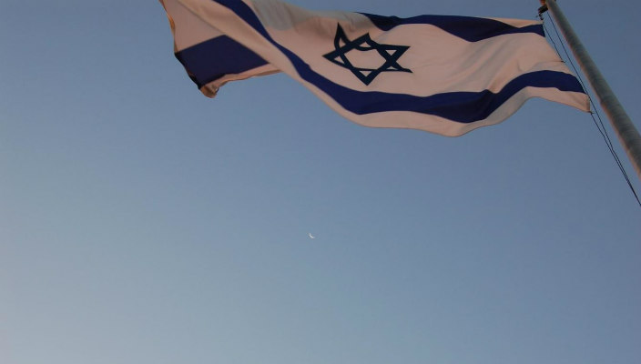 Israeli flag blowing against the blue sky