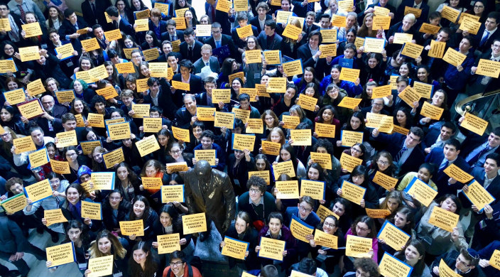 Aerial view of hundreds of teens holding yellow signs that read JEWS DEMAND ACTION