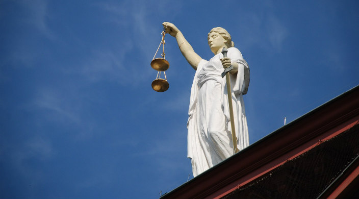 White marble statue of justice holding brass scales