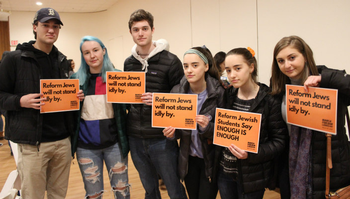 Teens and young adults with Reform Movement gun violence prevention signs
