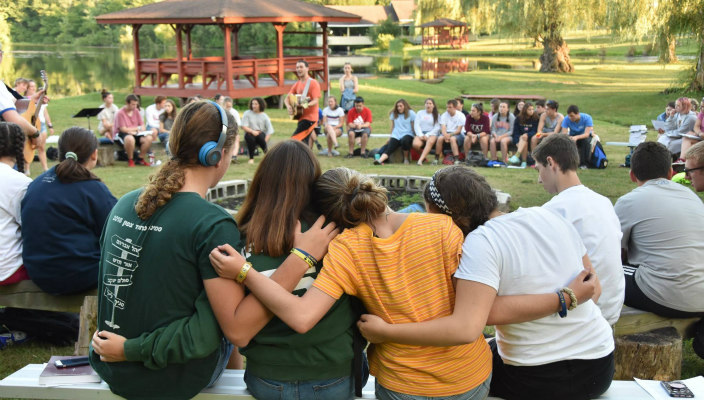 Campers sit on a bench with their arms around one another and their backs to the camera as they sit in a circle with camp in the background