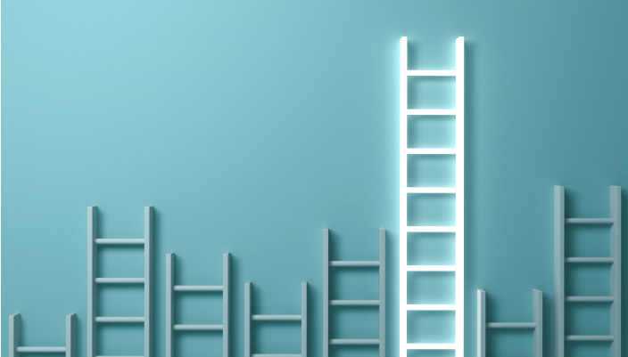 White ladders of all reaches laid against a blue background with the highest ladder glowing as if to represent success