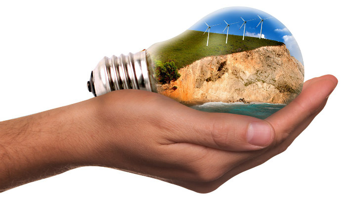 Graphic of a hand holding a lightbulb that appears to contain a mountain and windmills