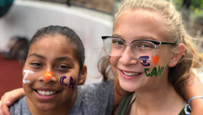 Two smiling tween girls with I LOVE CAMP written on their cheeks in face paint