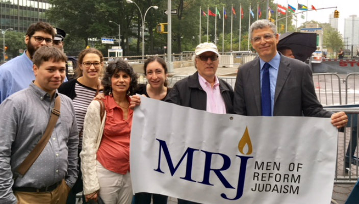Group of individuals standing behind a Men of Reform Judaism sign held by Rabbi Rick Jacobs
