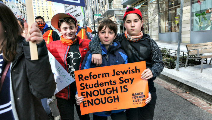 Three teen boys holding signs that read REFORM JEWISH STUDENTS SAY ENOUGH IS ENOUGH