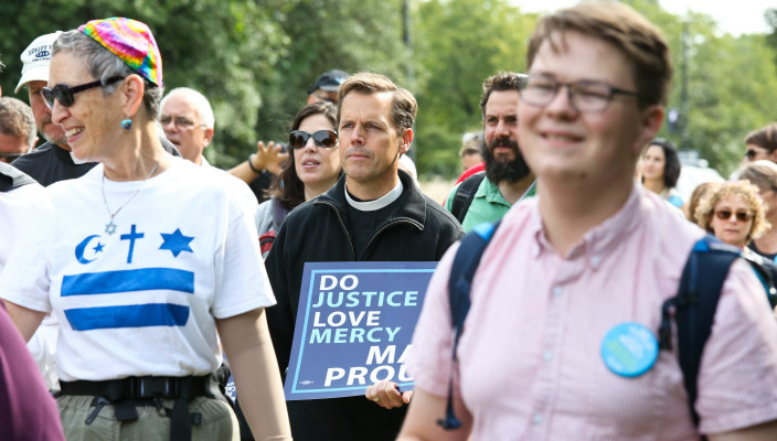 Three individuals as part of a larger group marching in some sort of event and carrying a sign that reads DO JUSTICE LOVE MERCY MARCH PROUDLY