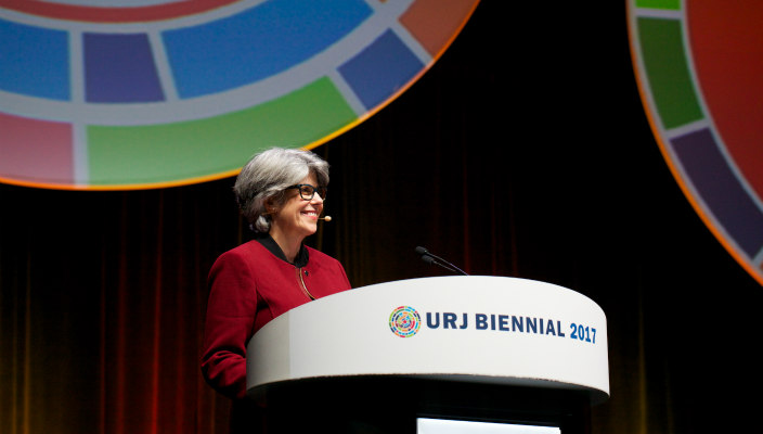URJ VP of Youth Miriam Chilton in a red blazer in front of the URJ Biennial logo