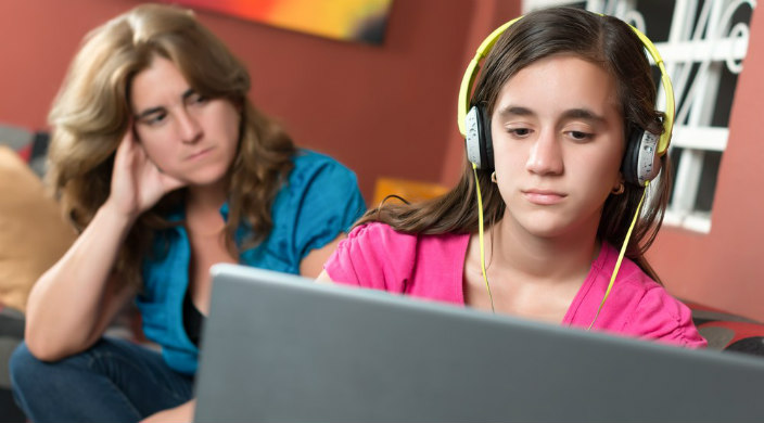 Concerned mom look over her teen daughters shoulder as the teen looks at the screen of her laptop