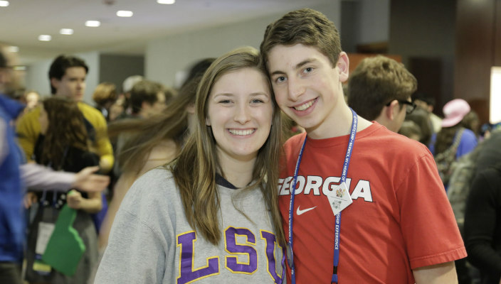 Male and female graduating NFTY seniors with their arms around one another while wearing college tee shirts