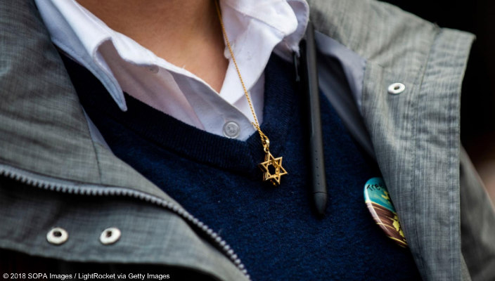 Closeup of a person wearing a Star of David necklace against a blue sweater