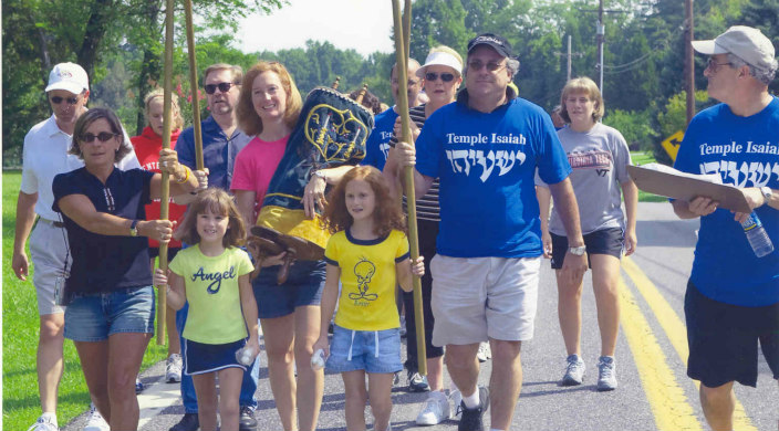Group of adults and children wearing Temple Israel shirts and carrying a Torah outdoors