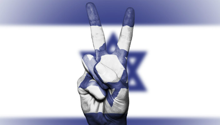 Fingers giving the peace sign in front of an Israeli flag