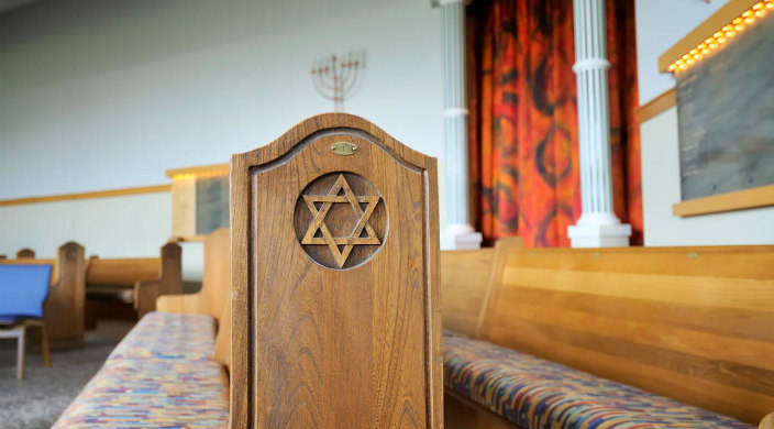 Side view of empty synagogue pews zoomed in on wooden carving of Star of David design at the ends of the pews