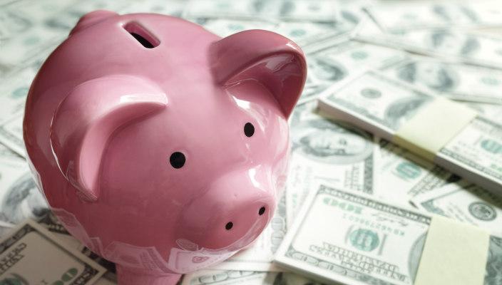 Pink piggy bank sitting atop piles of money