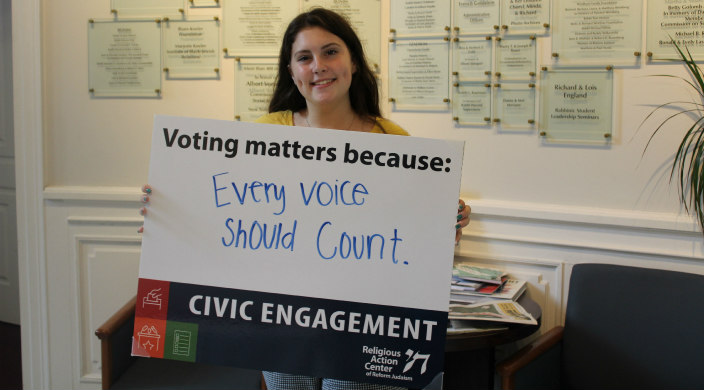 Young woman holding a sign that reads Voting counts because every voice should matter