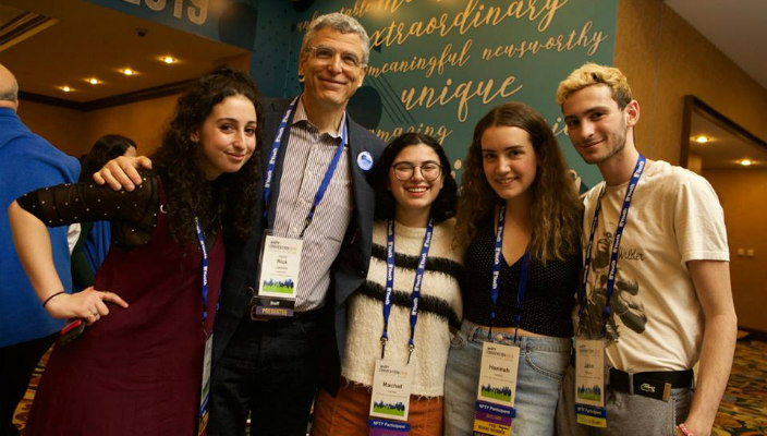 Rabbi Rick Jacobs poses with three smiling teens in NFTY Convention badges