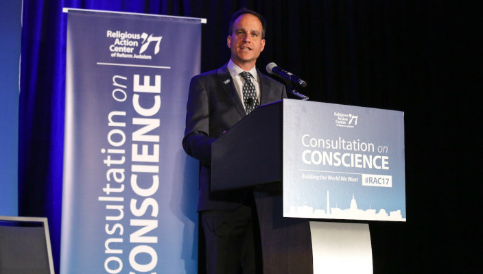 Rabbi Jonah Pesner speaking at a dais at the Consultation of Conscience