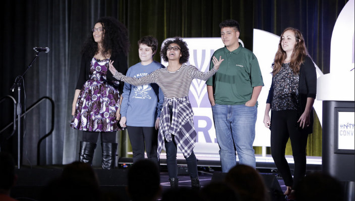 Group of multiracial teens and adults standing on stage in front of a NFTY sign