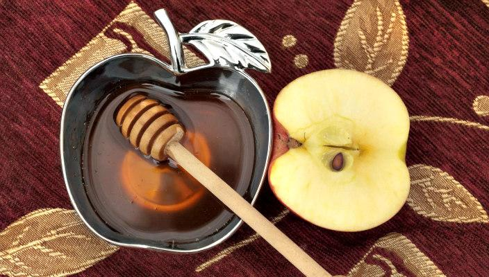 Apple shaped bowl of honey with a honey dipper in it and half an apple on a table next to it