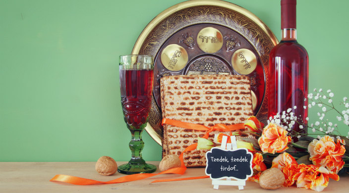 Passover seder setup with a small chalkboard that reads Tzedek Tzedek Tirdof