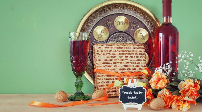 Passover seder setup with a small chalkboard that reads Tzedek Tzedek Tirdof