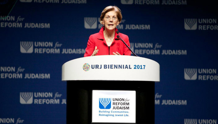 Senator Elizabeth Warren wearing a red blazer against a blue background with the Union for Reform Judaism name and logo
