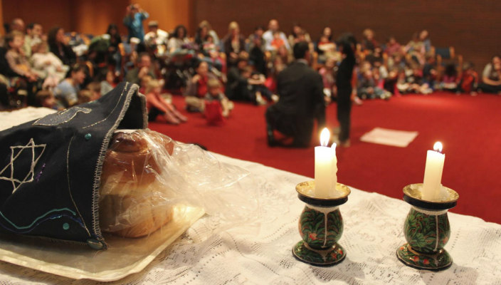 Challah and candlesticks at the head of a congregation