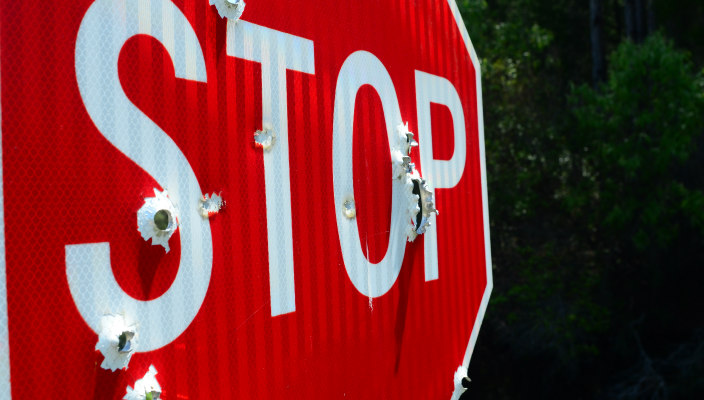 Closeup of a stop sign riddled with bullets
