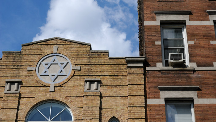 Brick synagogue building with a large stone Star of David above the door