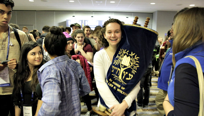 Smiling teen girl holding a Torah in a crowd of teens