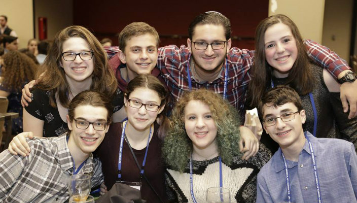 Group of smiling teens together at Shabbat dinner