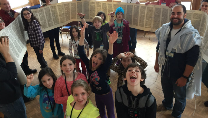 Kids standing around unrolled Torah scroll