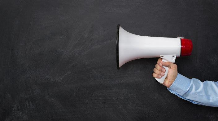 Male hand holding a white megaphone against a chalkboard