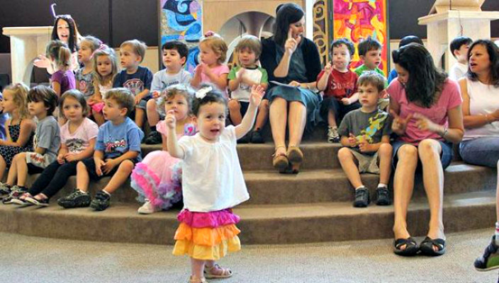 Toddler at synagogue programming with arms raised as if dancing