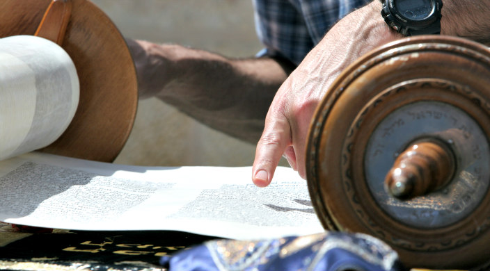 Closeup of a mans hand reading Torah on a table outdoors