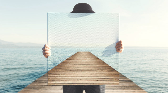 Person on a dock holding a clear pane of glass as if to represent transparency