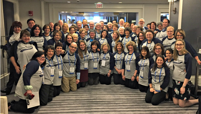 Large group of smiling URJ staffers and lay leaders in matching URJ tee shirts posing together at URJ spring training