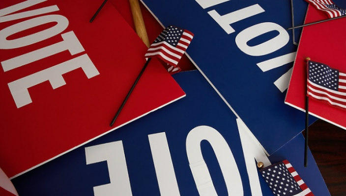A pile of voter signs in red white and blue with small American flags sprinkled atop them