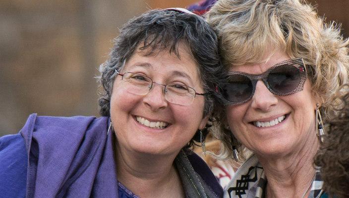 Two smiling middleaged women wearing kippot