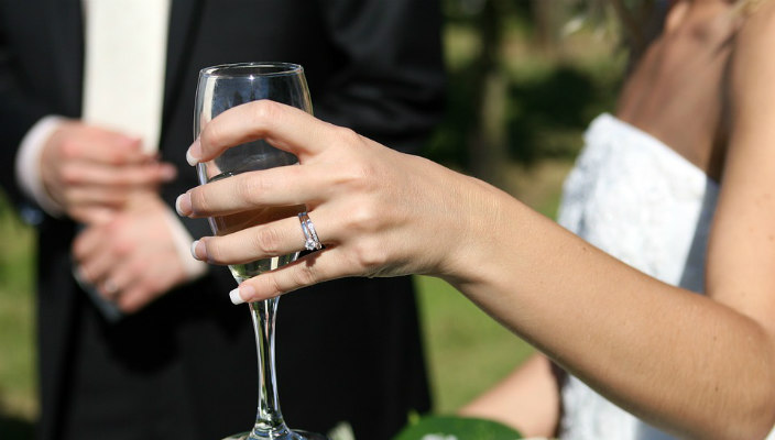 Closeup of a bride holding a glass of champagne with groom in the background behind her
