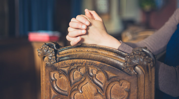 Closeup of a woman's hands resting on a wooden pew