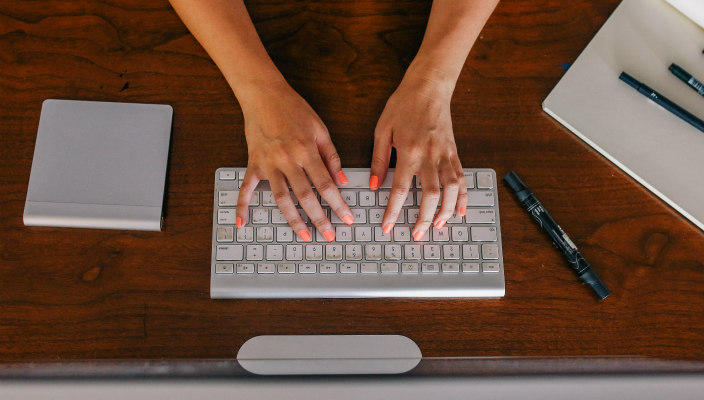 Aerial view of a womans hands on a white keyboard as if typing