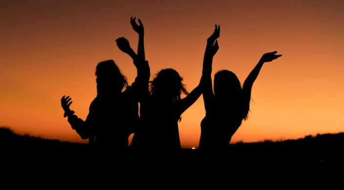 Silhouette of three women cheering against a sunset