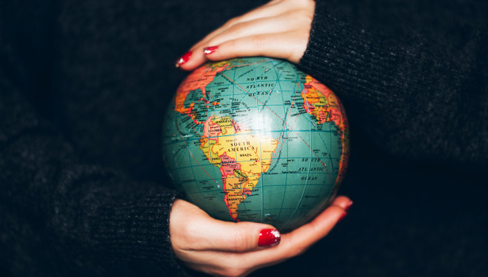 Womans hands with red painted fingernails holding a small globe replica