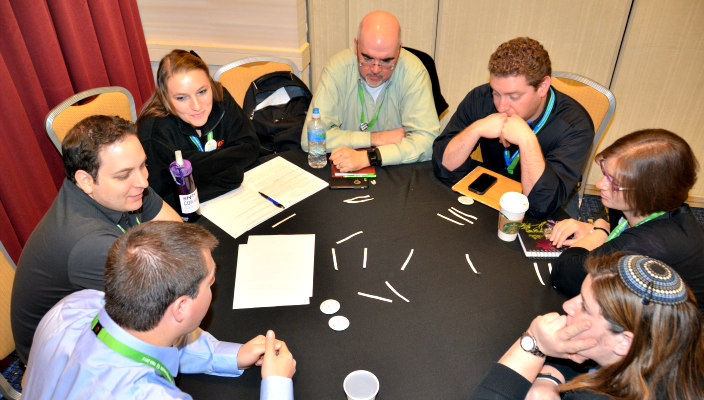 Youth professionals gathered around a table working together with notebooks and pens scattered across the surface of the table