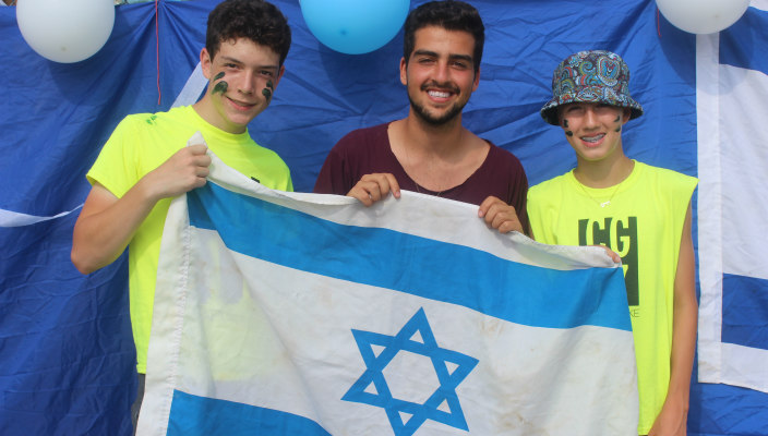 Three smiling male teens holding an Israeli flags