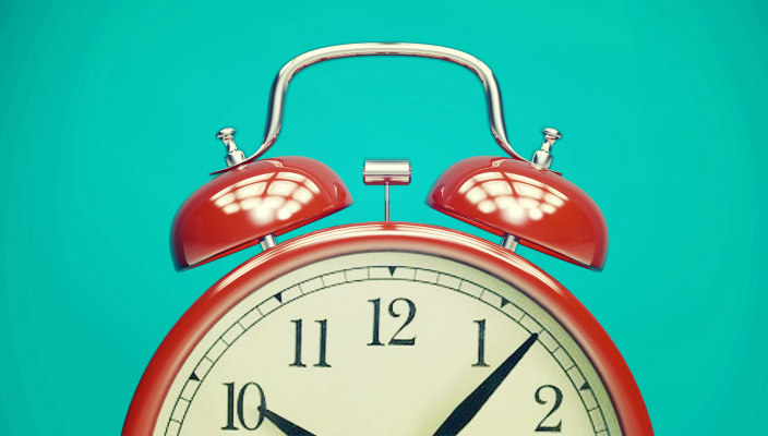 Old fashioned red alarm clock with white face and bells on top against a turquoise background