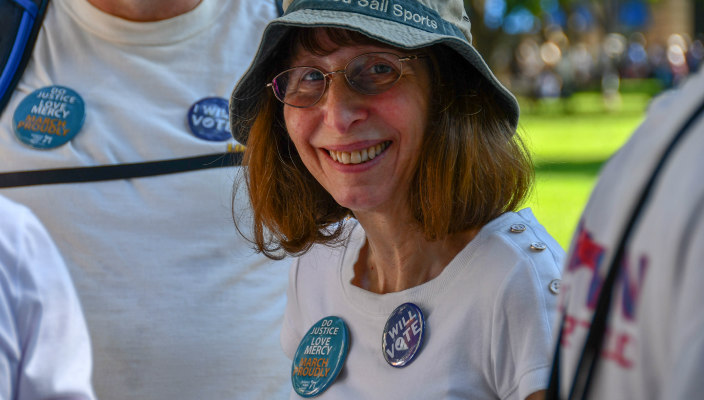 Woman smiling at the camera while wearing Jewish social justice buttons on her shirt