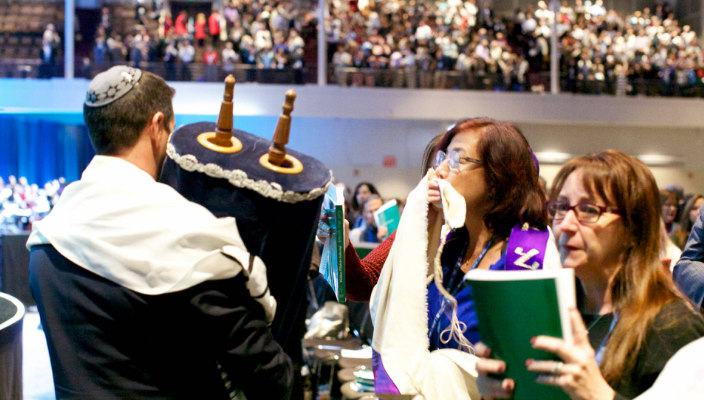 Man walking the Torah through aisles of people at the Biennial as they kiss the scroll